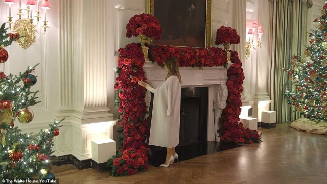 Melania can bee seen adding the final touches to the decorations, including this pile of red roses lays across one fireplace
