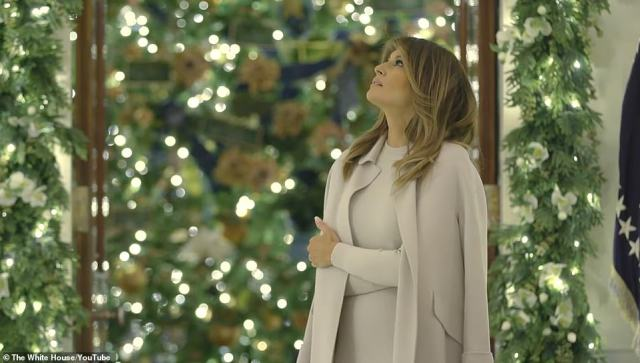 Melania Trump, pictured, officially unveiled the White House Christmas decorations on Sunday night in a festive video which showed the first lady adding the final touches to the patriotic display, dubbed 'The Spirit of America'