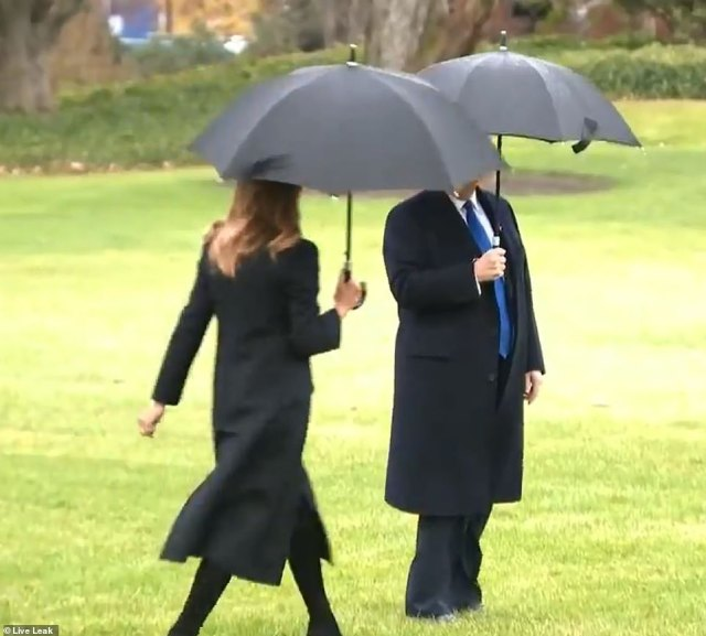 There she is: Melania soon caught up to her husband, after walking quickly across the wet White House Lawn
