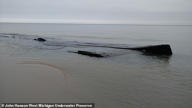 A mysterious shipwreck believed to be a barge that sank 90 years ago has been uncovered after a storm surge in Lake Michigan