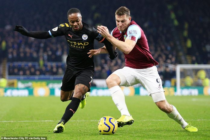 Raheem Sterling battles for the ball with Burnley striker Chris Wood as both sides look to take control of the game