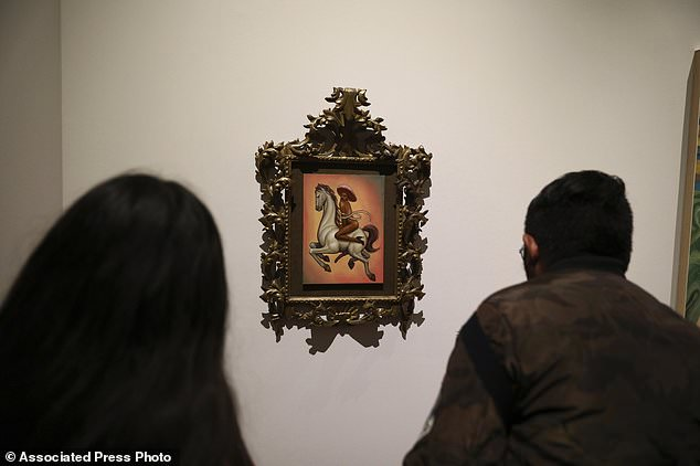 People view the painting showing 1910-17 Mexican revolutionary hero Emiliano Zapata nude, wearing high heels and a pink, broad-brimmed hat and straddling a horse
