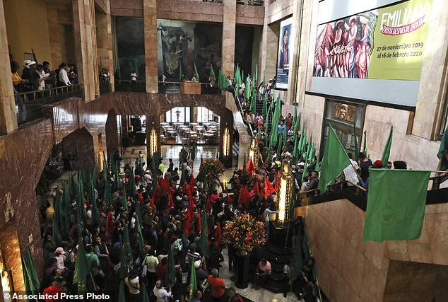 Farm workers block the entrance of the Fine Arts Palace in Mexico City to protest against a painting showing 1910-17 Mexican revolutionary hero Emiliano Zapata nude, wearing high heels and a pink, broad-brimmed hat, straddling a horse