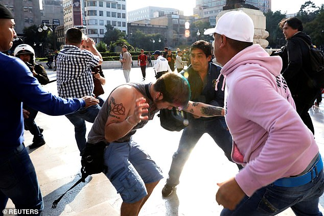 A man is attacked Tuesday outside the Fine Arts Palace in Mexico City during a brawl that pitted descendants and supporters of the Mexican revolutionary hero against LGBT activists, who showed up to defend sexual diversity and protest the painting's removal