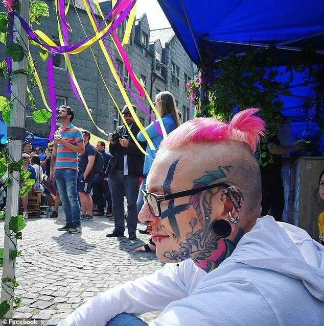 Mr Pickersgill shows off the upside-down cross inked on his face, his pink hair and ear spacer