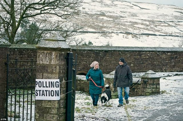 Philip, 61, and Julie Jones, 60, outside the polling station in Nenthead, on the Cumbria and Northumberland border, with snow, ice and freezing rain forecast across the UK today