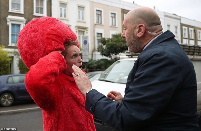 A member of Jeremy Corbyn's security detail argues with a person dressed as Sesame Street character Elmo, who is standing against Boris Johnson in Uxbridge