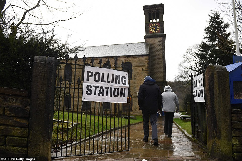 A couple arrive to vote in the rain at a polling station in Dobcross nearOldham, in Greater Manchester