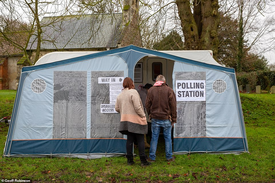Voters in the village of Carlton, Cambridgeshire voting in a caravan for today's general election