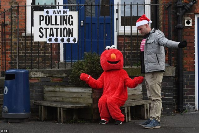 A man in a santa hat and a man in an Elmo costume outside the polling station at Pakeman Primary School in Islington, north London