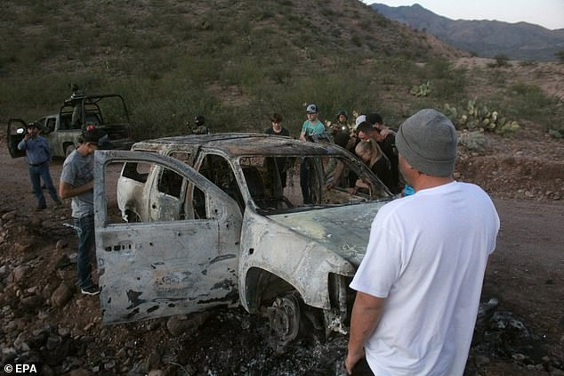 Pictured: members of the LeBaron family looking at the charred remains of their family member's SUV after it caught fire