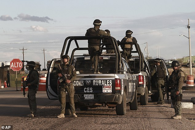 Chihuahua state police stand at a checkpoint in northern Mexicao after hitmen ambushed members of the LeBaron family