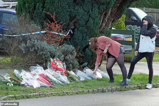 People place flowers at the scene on Hazel Way in Crawley Down, West Sussex