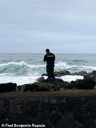 An officer is seen near the water during a search