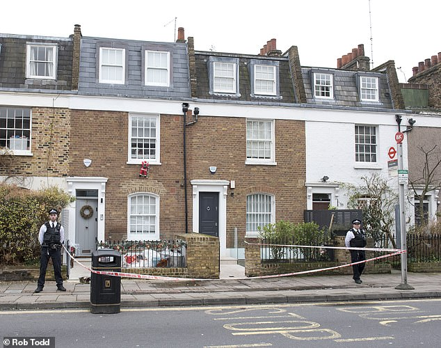 A police cordon remains outside the house in Battersea where the 36-year-old was shot to death