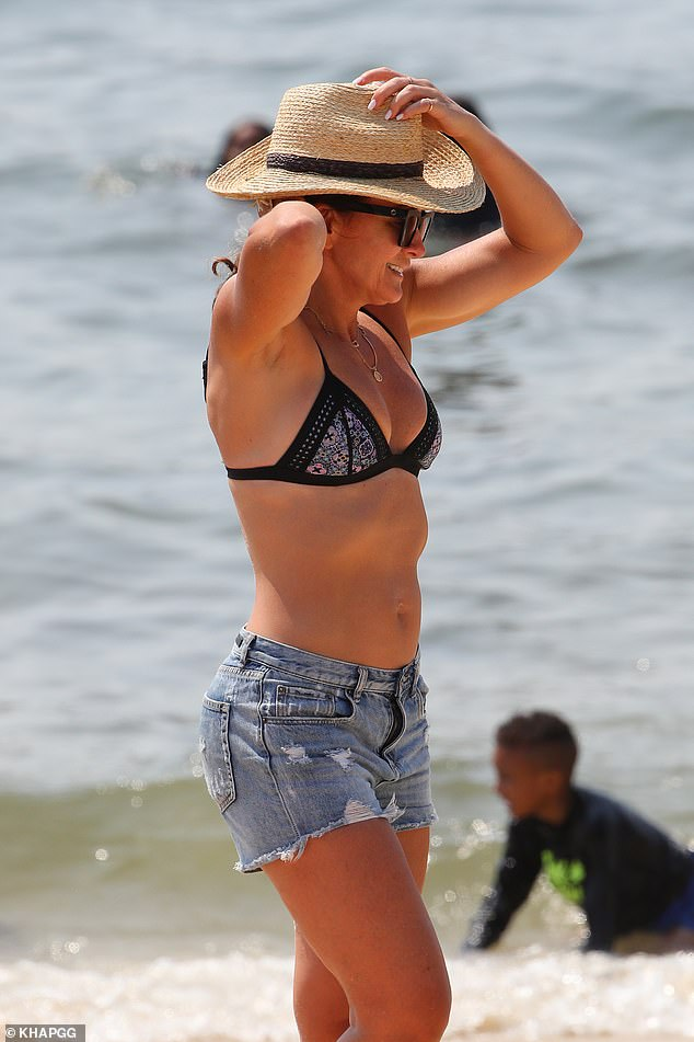 Ready to go: Michelle later got dressed in a pair of denim shorts as they left the beach