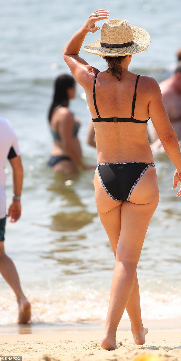 That's cheeky! Michell's swimsuit showed off her sculptured pins and pert derriere