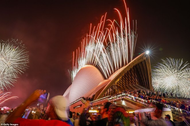 Fireworks explode from the Sydney Opera House as crowds of revellers gather around to watch the display
