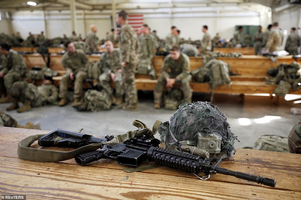 U.S. Army paratroopers of an immediate reaction force wait to board their C-17 transport aircraft to leave Fort Bragg