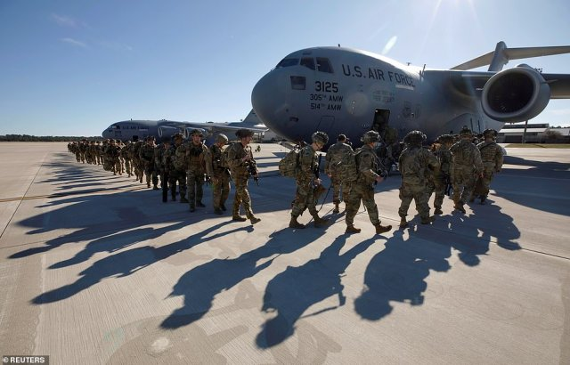 U.S. Army paratroopers of an immediate reaction force from the 2nd Battalion, 504th Parachute Infantry Regiment, 1st Brigade Combat Team, 82nd Airborne Division, line up to board their C-17 transport aircraft as they leave Fort Bragg