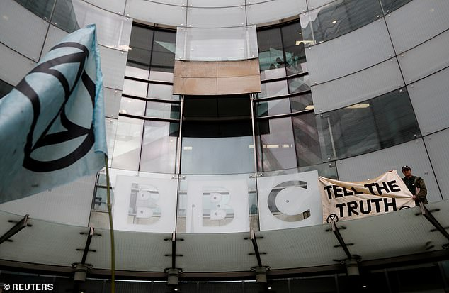 BBC received a record 24,435 complaints in just a two-week period during the election campaign should be cause for concern at the BBC but its reaction was far too defensive (pictured, a protester holds a banner during an Extinction Rebellion demonstration on October 11)
