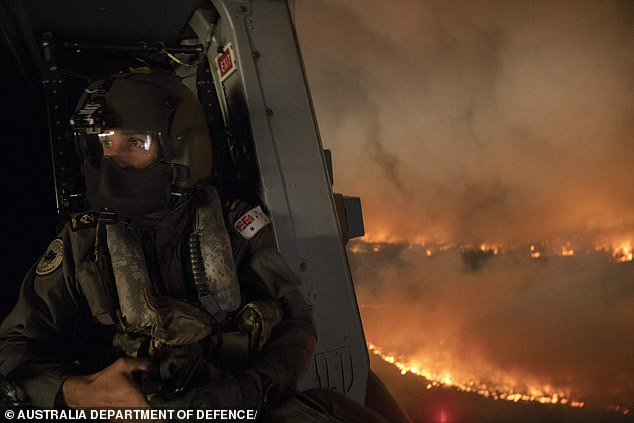 A Defence Force aircrewman monitoring the Tianjara fire from a helicopter in Moreton, NSW, on December 21. Up to 3000 Defence Force reservists have now been called up