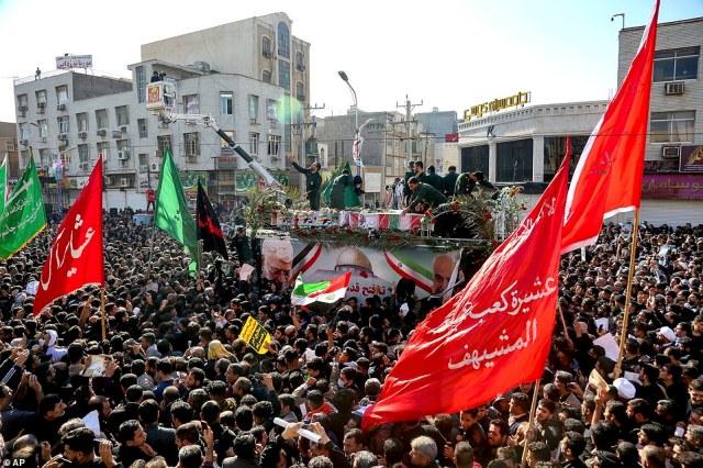 Udrapowane flagami trumny gen Qassem Soleimani i jego towarzysze, którzy zostali zabici w Iraku podczas amerykańskiego uderzenia dronów, są przewożeni ciężarówką otoczoną przez żałobników podczas ich pogrzebu w południowo-zachodnim mieście Ahvaz w Iranie w niedzielę