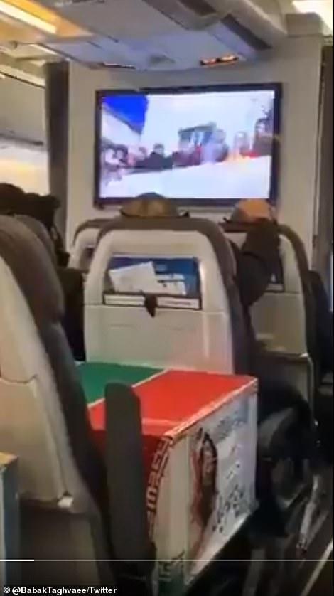 Tekturowe trumny z twarzą martwego człowieka w środku narysowane z boku były widziane na siedzeniach pasażerów odrzutowca zmierzającego do Teheranu