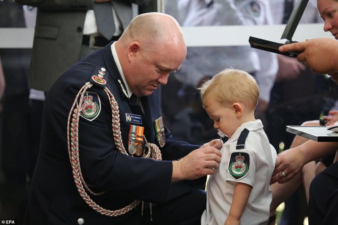 RFS commissioner Shane Fitzsimmons pins Mr Keaton's service medal on his young son, a moment that has become a lasting image of the bushfire disaster