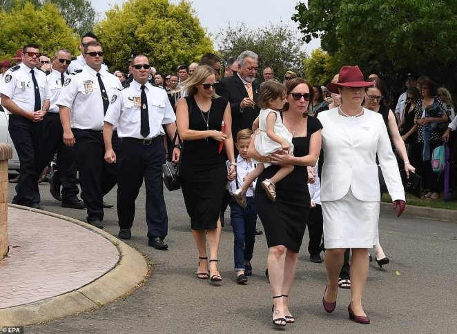 Mrs O'Dwyer and her daughter Charlotte (front) were joined by members of the Horsley Park RFS in leading the procession out of the church grounds