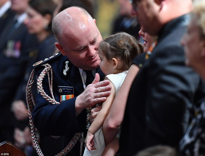 Mr Fitzsimmons gives young Charlotte a hug after presenting her with the service medal posthumously awarded to her father
