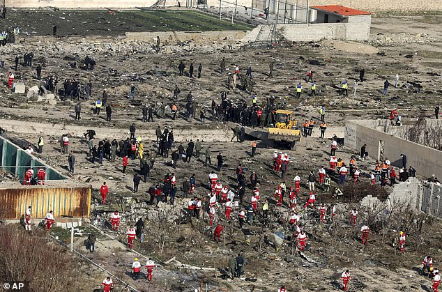 Rescue workers search the scene where the Ukrainian plane crashed after takeoff from Tehran's international airport early Wednesday