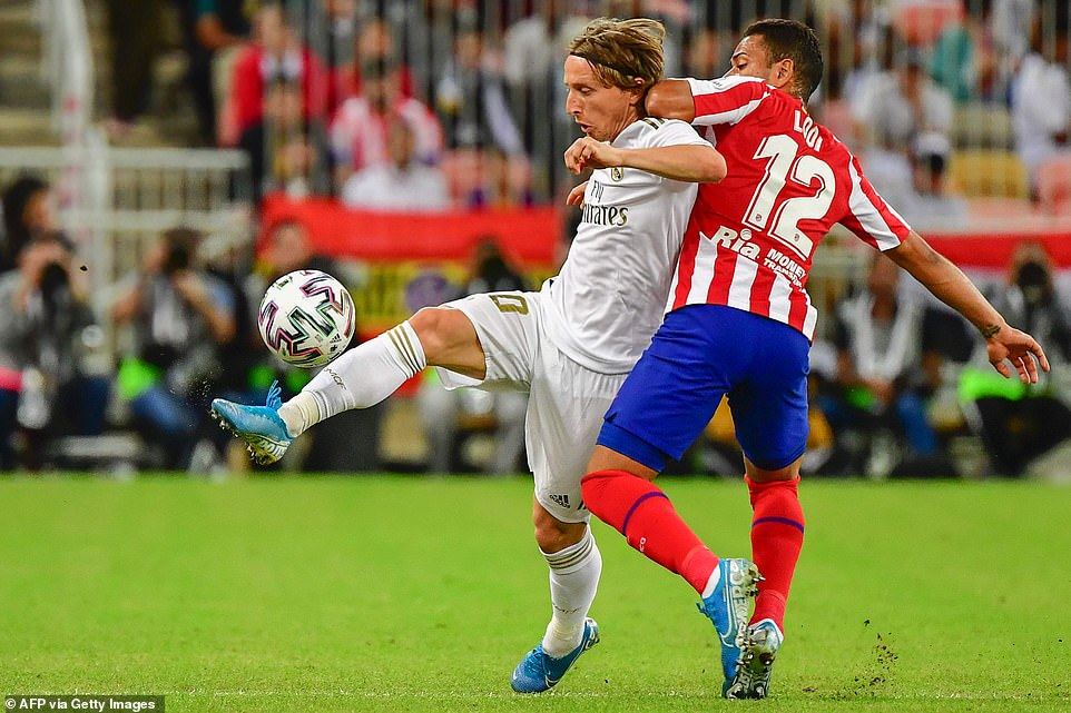 Real Madrid's Luka Modric tries to control the ball and overtake Renan Lodi, defender of Atletico Madrid
