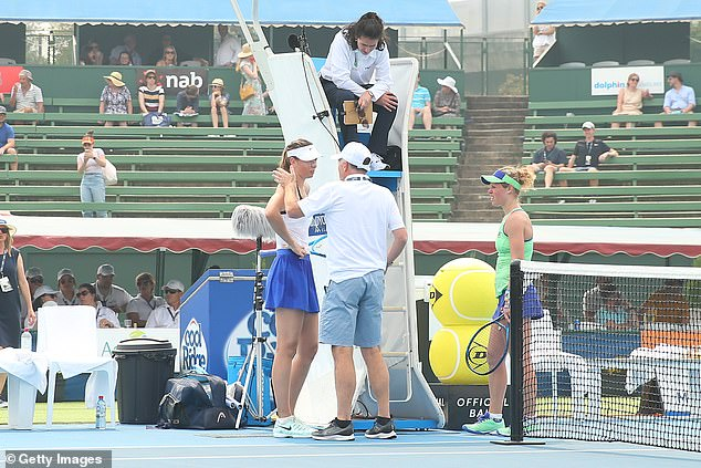 Sharapova (left), with Laura Siegemund (right), talking to officials before the game is called off