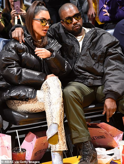Matching: Kim and Kanye coordinated in oversized black jackets, with the reality TV star donning a hooded padded number and the rapper opting for a large windbreaker