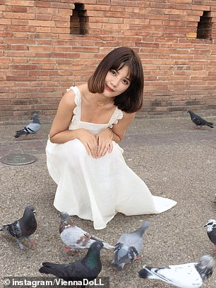 Pictured: The model poses with pigeons