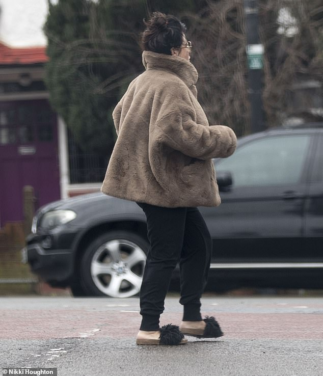 Making her own style rules: Jessie was pictured in an oversized fluffy coat and sandals during her rainy day outing