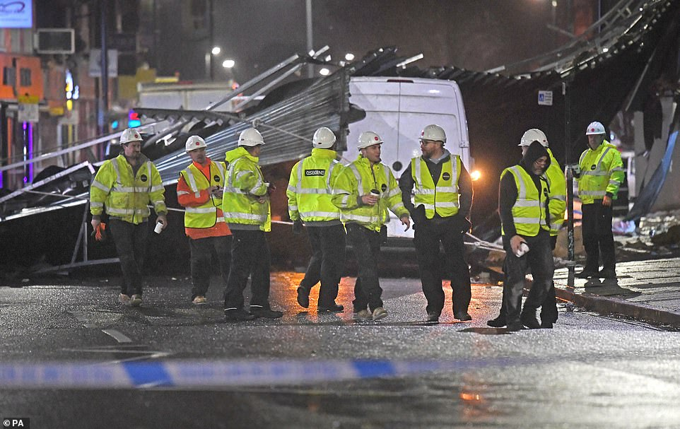 Construction workers in Slough yesterday evening after a roof was blown off a building onto the road amid strong winds