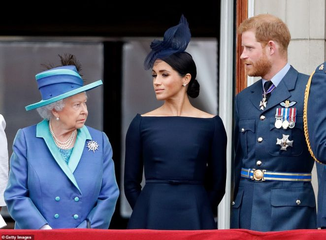 Queen Elizabeth II, Meghan, Duchess of Sussex and Prince Harry, Duke of Sussex watch a flypast to mark the centenary of the Royal Air Forcefrom the balcony of Buckingham Palace on July 10, 2018