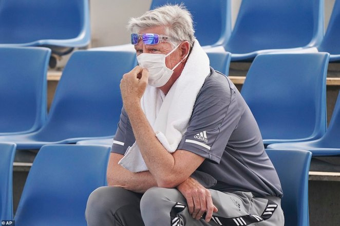 A spectator wears a mask as smoke haze shrouds Melbourne during an Australian Open practice session at Melbourne Park in Australia, Tuesday, Jan