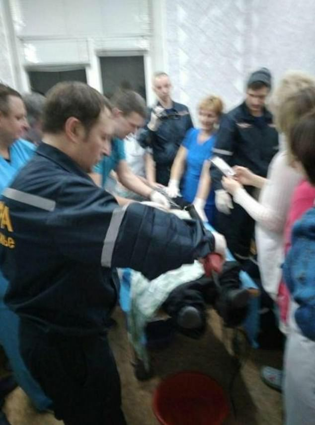 The rescue team are pictured using a circular saw to cut the nut constricting the man's penis in Zaporizhia, Ukraine on the day of his injury