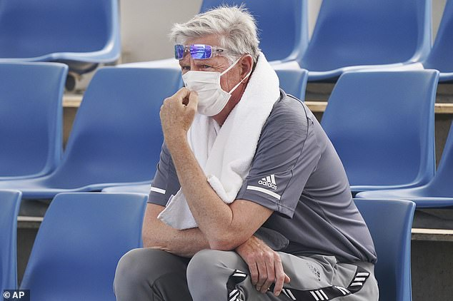 A spectator wears a mask as smoke haze shrouds Melbourne during an Australian Open practice session at Melbourne Park in Australia, Tuesday, Jan 14