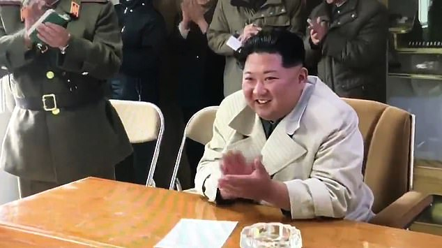Applause: Kim and his aides later gave the performers a warm reception after a display including songs, dance and musical instruments