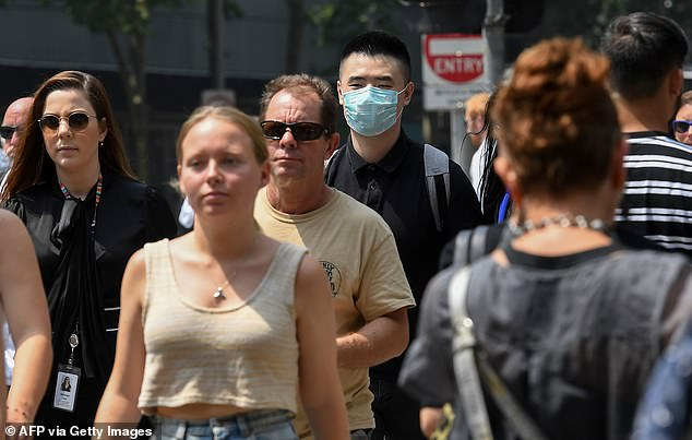 A man wears a mask while others brave the toxic smoke without today in Melbourne