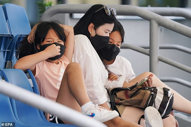 Spectators wear face masks to combat smoke haze during an Australian Open practise session at Melbourne Park in Melbourne, Australia today