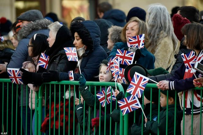 People hold Union Jack flags ahead of William and Kate meeting with the members of the public in Bradford today
