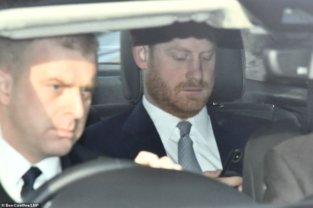 Prince Harry arrives at Buckingham Palace looking at his phone as he appears for the first time since quitting as a senior royal - and it could even be his swansong if no deal is struck with the Queen
