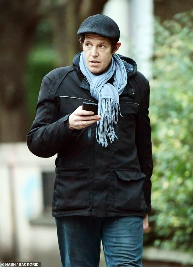 Relaxed:The filmmaker cut a casual figure in a black utility jacket, grey scarf and jeans during the stroll around Notting Hill