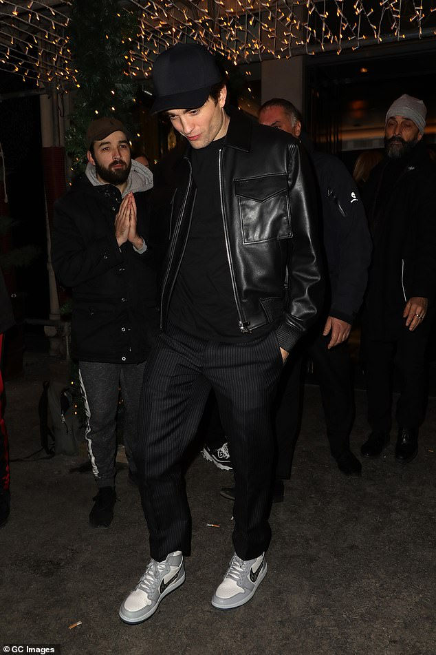Low-key: Robert teamed his look with grey trainers and a black flat cap as he headed out of the fashionable bash