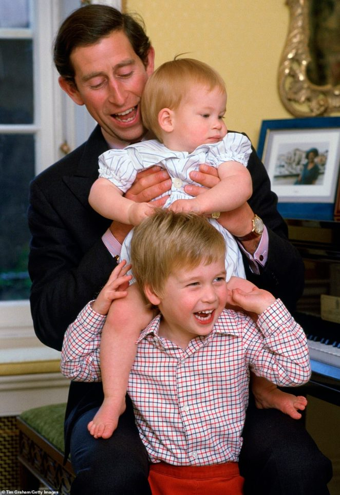Prince Charles laughs with his sons as he lifts Prince Harry onto Prince William's shoulders at Kensington Palace in 1985